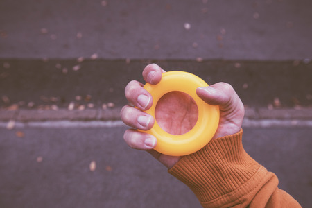 Male hand grips anti-stress rubber ring outdoors, close up