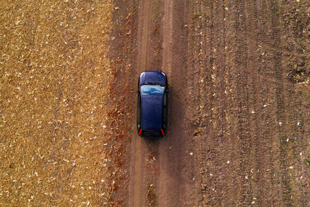 Aerial view of black car on dirt road through countryside, top view driving vehicle from drone pov