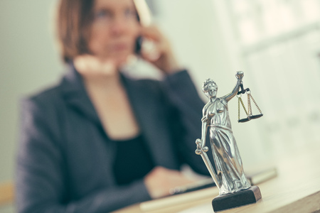 Attorney woman talking on mobile phone from her office desk, selective focus