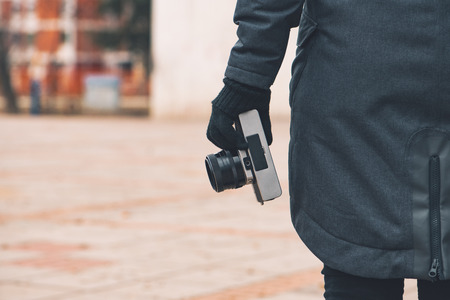 Hipster female photographer holding vintage SLR camera on street in winter, close up of hand Stock Photo
