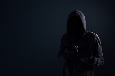 Hooded computer hacker with obscured face using digital tablet in cybercrime and cybersecurity concept, low key with selective focus Stock Photo - 116358261