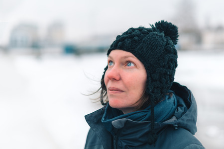 Portrait of concerned adult caucasian woman standing in snowy outdoors