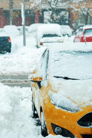 Automobile parking lot with cars covered in snow, parked vehicles in winter season with harsh traffic conditions