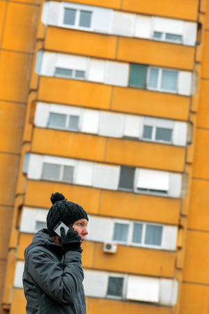 Woman talking on mobile phone on street in winter. Serious caucasian female during telephone conversation with ugly apartment building in background. 写真素材 - 116302645