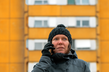 Woman talking on mobile phone on street in winter. Serious caucasian female during telephone conversation with ugly apartment building in background.