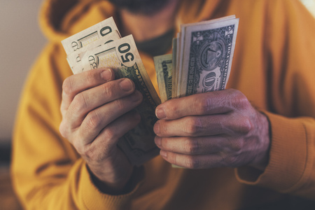 Casual man is counting american dollar banknotes, close up of hands with money