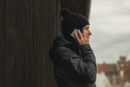 Worried woman talking on mobile phone on street on cold winter day
