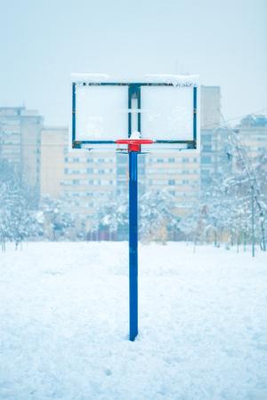 Frozen outdoor basketball hoop in winter snow on empty sport playground