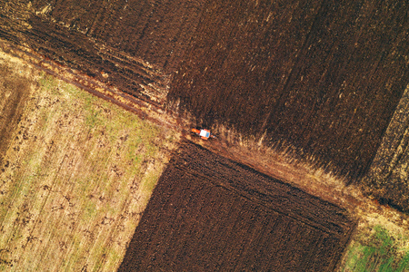 Aerial view of agricultural tractor plowing field in cold autumn afternoon from drone pov Stok Fotoğraf