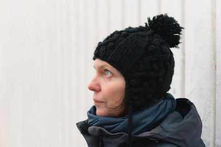 Portrait of concerned woman on the street looking up on cold winter day