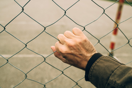 Male hand on chainlink fence, illegal immigration concept Standard-Bild - 118085411