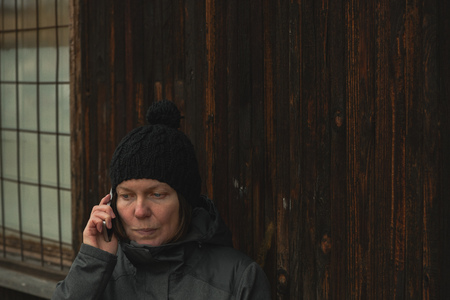 Serious woman talking on mobile phone on the street in cold winter afternoon Stock Photo - 118085707