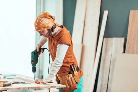 Female carpenter using electric drill in woodwork carpentry workshop, selective focus Standard-Bild - 118586320
