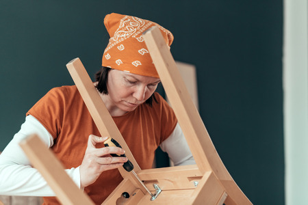 Female carpenter repairing wooden chair seat in small business woodwork workshop Stok Fotoğraf