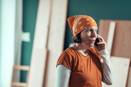 Female carpenter with head kerchief during serious mobile phone conversation with client in carpentry woodwork workshop Stock fotó