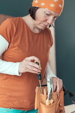 Female carpenter organizing tool belt set in woodwork workshop
