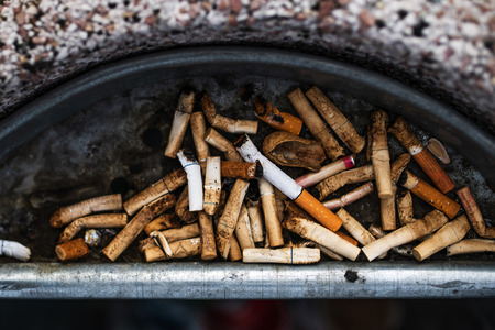 Cigarette butts in an ashtray on city street, top view