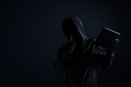 Hooded computer hacker with obscured face using digital tablet in cybercrime and cybersecurity concept, low key with selective focus