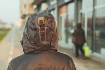 Rear view of hooded female person walking the city street in cold winter afternoon