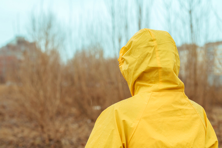 Rear view of woman in raincoat looking into distance on cloudy rainy winter day