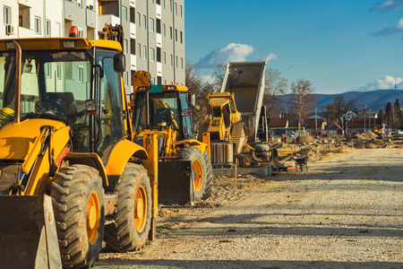 Construction vehicle with loader on building site, industrial heavy machinery