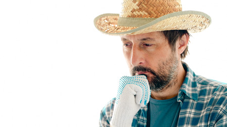 Portrait of thoughtful farmer in contemplative pose with hand on his chin isolated on white background.