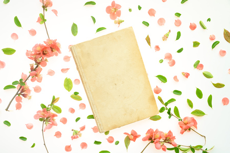 Old book mock up with springtime floral decoration, top view flat lay copy space