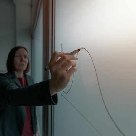 Businesswoman drawing graph on whiteboard in office while presenting business results during corporate meeting