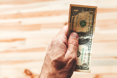 Man paying with one US dollar bill, close up of male hand holding american paper currency Imagens