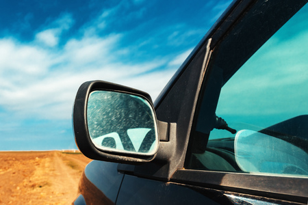 Wing mirror of a car on dirt country road in sunny summer afternoon Фото со стока