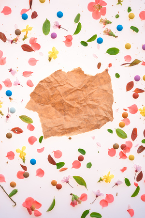 Piece of crumpled paper over colorful springtime background o flower petals and leaves as mock up copy space Banco de Imagens