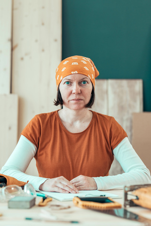 Portrait of confident female carpenter wearing headscarf bandana in small business woodwork workshop