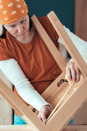 Female carpenter tape measuring wooden chair seat in small business woodwork workshop, close up of hands, selective focus