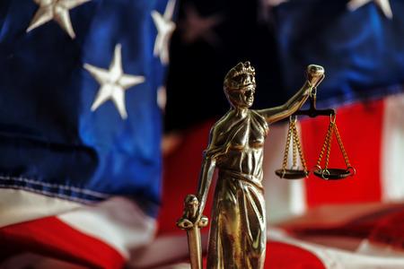 La ley y la justicia en los Estados Unidos de América, la estatua de la Señora Justicia con la bandera de Estados Unidos en el fondo, el enfoque selectivo