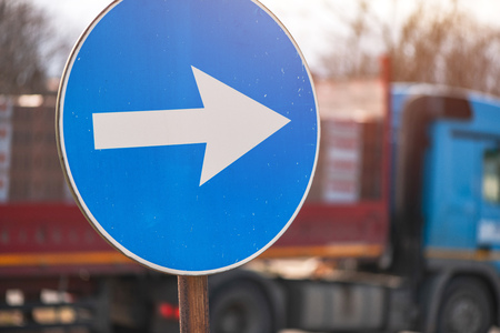 Proceed in direction arrow traffic sign on the street with defocussed vehicle in background Stock fotó