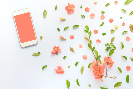 Smartphone mock up with springtime floral decoration, flat lay top view image of modern contemporary mobile phone device with blank screen