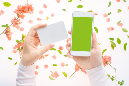 Springtime business card and smartphone in female hands mock up with colorful floral decoration