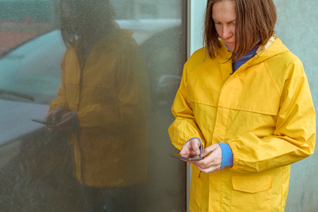 Woman in yellow raincoat texting on mobile phone outdoors on rainy day