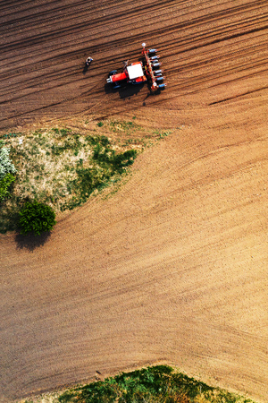 Farmer and tractor with seeder from drone pov, aerial view of agronomist preparing machinery for sowing, top view Stock Photo