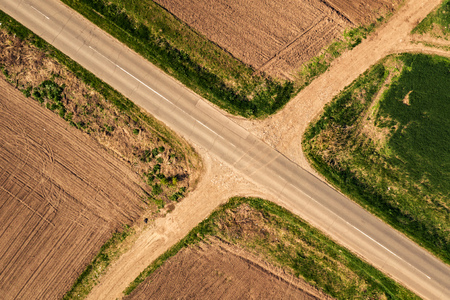 Aerial view of roadway and dirt road intersection, top down from drone pov Reklamní fotografie
