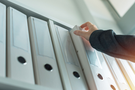 Businesswoman browsing through ring binder file documentation archives o the shelf in business office, close up of hand 版權商用圖片