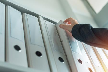 Geschäftsfrau durchsucht die Dokumentationsarchive der Ringbuchdatei im Regal im Geschäftsbüro, Nahaufnahme von Hand Standard-Bild