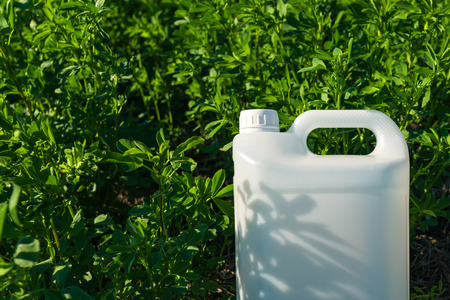 Pesticide jug mock up in clover field, crop protection concept