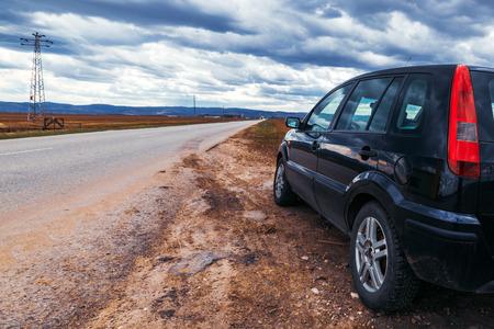 L'auto rotta si è fermata per strada in un giorno di tempesta, nuvole drammatiche nel cielo