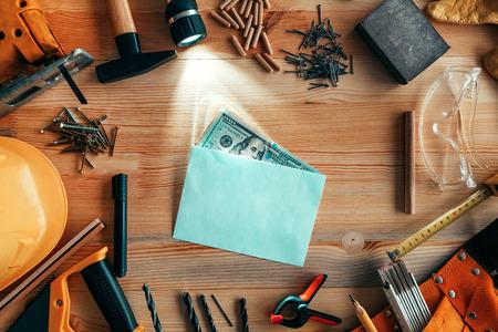 Money in envelope on carpentry woodwork workshop desk, top view