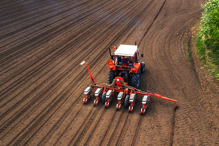 Aerial view of tractor with mounted seeder performing direct seeding of crops on plowed agricultural field. Farmer is using farming machinery for planting process.