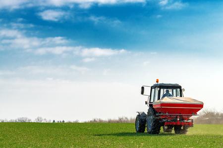 Granjero irreconocible en tractor agrícola está fertilizando el campo de cultivo de trigo con nutrientes fertilizantes NPK