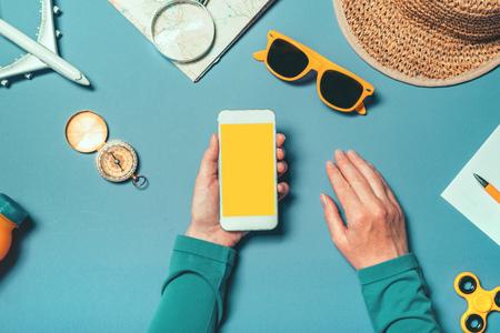 Maqueta de teléfono inteligente en concepto de vacaciones de verano, mujer sosteniendo teléfono móvil con pantalla en blanco como espacio de copia, vista superior con accesorios de verano dispuestos en plano