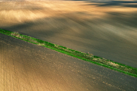 Aerial view of dried irrigation ditch canal through agricultural field during hot summer season, drone point of view