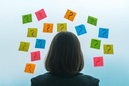 Zakenvrouw geconfronteerd met vragen en uitdagingen in zakelijke situatie, achteraanzicht van vrouwelijke zakenman kijken naar vraagtekens geschreven op kleurrijke plaknotitie papier